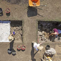 """Fig. 8. Overhead photograph of the excavation in progress at trenches 5 and 6. One of the very large masses of travertine (called """"monsters"""" in the text) has just been excavated, and it is now sitting on the west side of trench 5. (photo M. Holobosky)"""